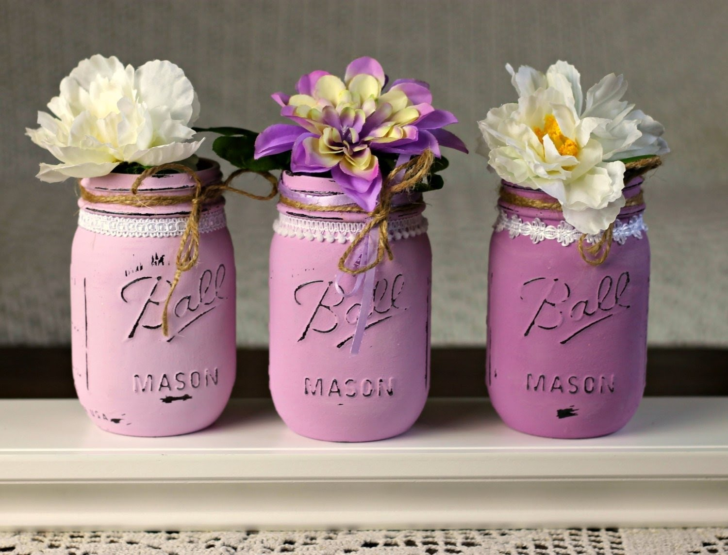 Distressed Antiqued Vintage painted bottles with silk flowers featuring different designs